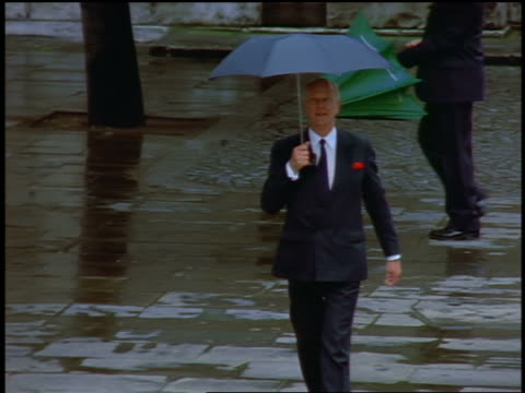 slow motion high angle middle aged businessman walking with umbrella in rain / London