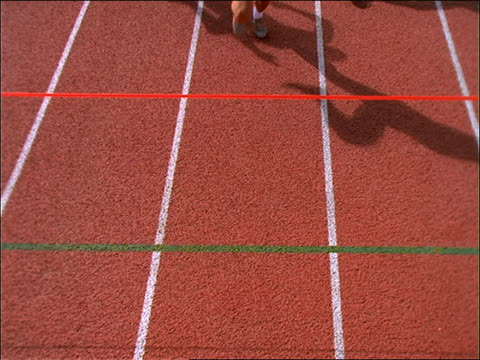slow motion high angle of male runners crossing finish line on track