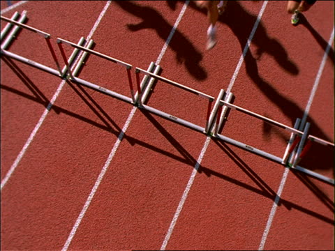 stockvideo's en b-roll-footage met slow motion high angle of male runners jumping hurdles on track - elasthaan