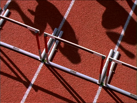 slow motion high angle of male runners jumping hurdles on track