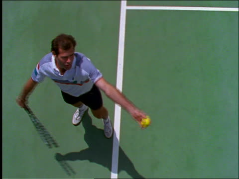 slow motion high angle of man serving ball in tennis match - serving sport stock videos and b-roll footage