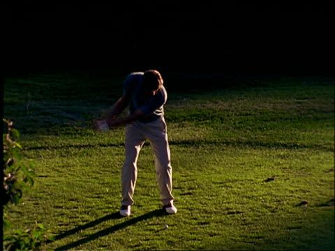 vídeos de stock, filmes e b-roll de slow motion high angle of man teeing off on golf course - camisa pólo