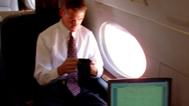 shaky slow motion high angle ms pan over-the-shoulder businessman typing on laptop facing man using pda in airplane - shaky stock videos & royalty-free footage