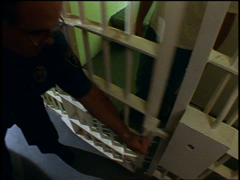 slow motion high angle prison guard locking male prisoner into prison cell / prisoner grabs bars with hands - jail cell stock videos & royalty-free footage