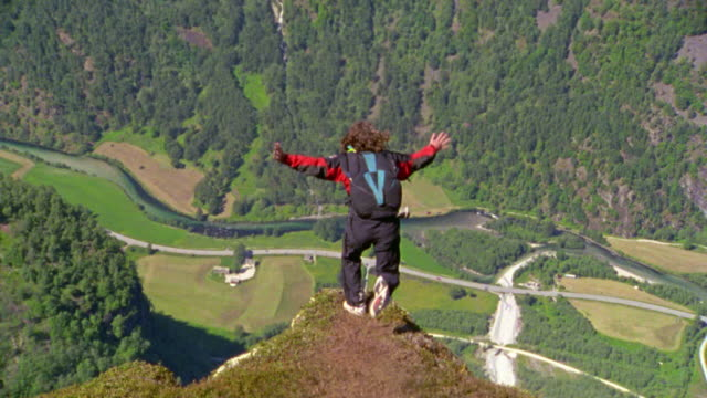 slow motion high angle rear view man base jumping off cliff + spinning around / kjerag rock, near stavanger - cliff stock videos & royalty-free footage