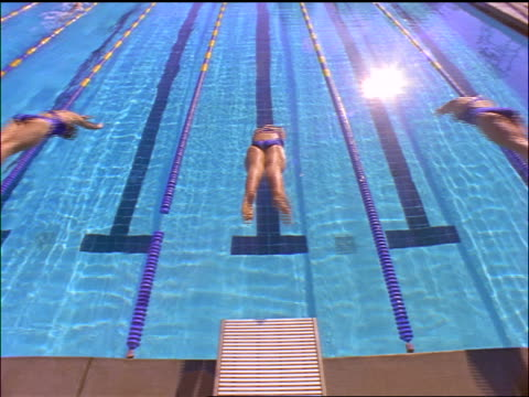 slow motion high angle REAR VIEW three women diving from starting block into swimming pool in race