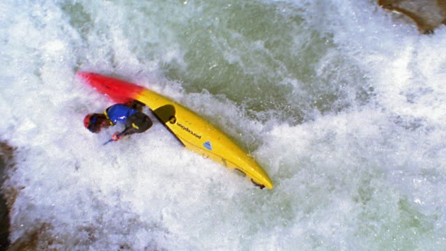 Slow motion high angle tilt down person kayaking in white water rapids and going over small waterfall