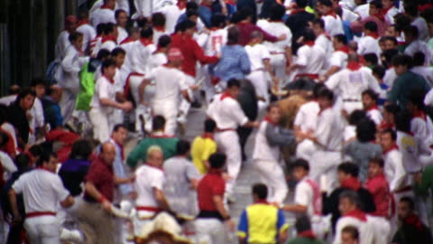 stockvideo's en b-roll-footage met slow motion high angle tilt up rack focus people running with bulls on city street / running of the bulls / pamplona, spain - stier mannetjesdier