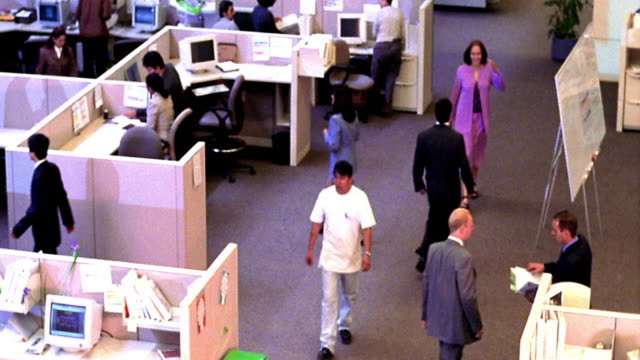 slow motion high angle time lapse office workers working + walking around in large open office with cubicles