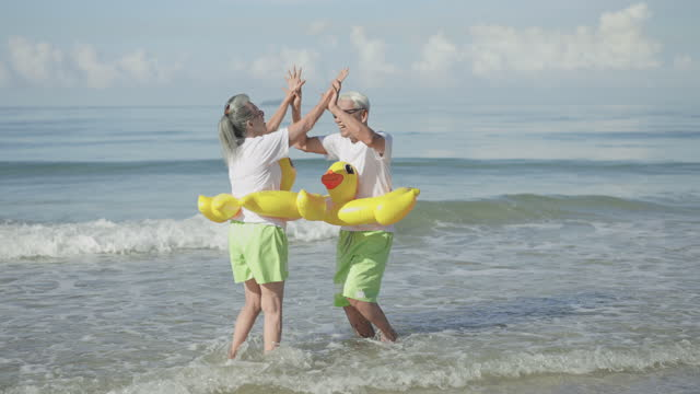slow motion high angle view of a mature couple running to sea with feeling positive emotion, excited in couple cloth, white t-shirt, green shorts, yellow swimming ring at the beach, retirement senior adult in holiday summer. - swimming shorts stock videos & royalty-free footage