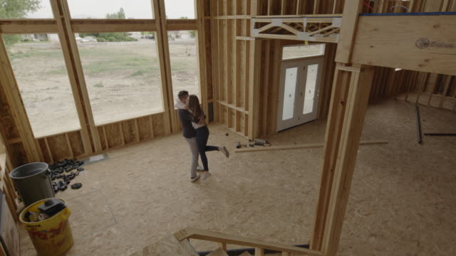 slow motion high angle view of couple hugging in interior of home under construction / pleasant grove, utah, united states - timber stock videos & royalty-free footage