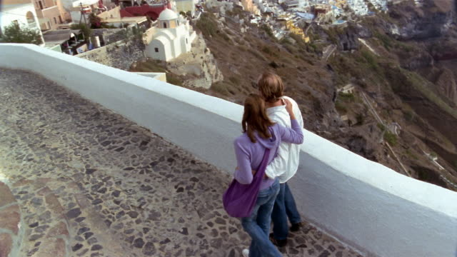 slow motion high angle wide shot couple walking with arms around each other along wall with view of santorini / greece - santorini stock videos and b-roll footage
