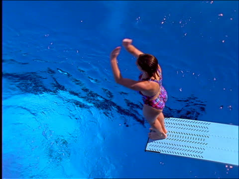 slow motion high angle woman flipping over and diving into swimming pool