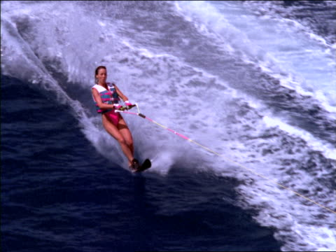 slow motion high angle woman waterskiing on ocean in tahiti / releases tow rope - waterskiing stock videos & royalty-free footage