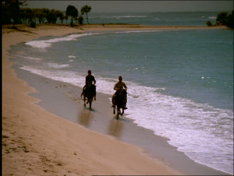 slow motion high angle zoom out pan of 2 men riding horses in surf on nusa dua beach / bali / indonesia - freizeitreiten stock-videos und b-roll-filmmaterial