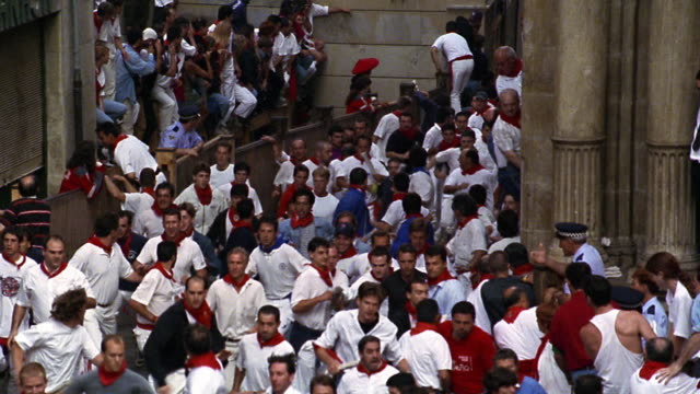 vídeos y material grabado en eventos de stock de slow motion high angle zoom out pan crowd of people running away from bulls / running of the bulls / pamplona, spain - grupo de animales