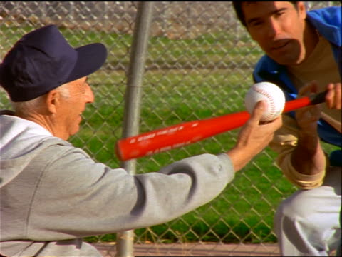 slow motion hispanic father helping son practice batting ball held by grandfather - baseball bat stock videos & royalty-free footage