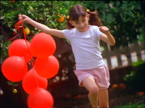 slow motion Hispanic girl with pigtails holding red balloons + running towards camera
