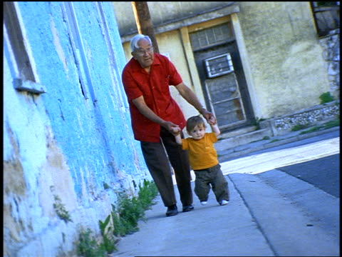 CANTED slow motion Hispanic grandfather walking with toddler outdoors by houses with peeling paint
