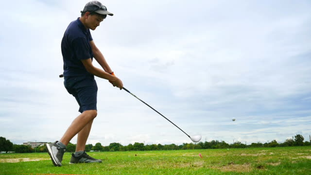 slow motion: hitting golf ball at golf course player exercise for good health - golf swing motion stock videos & royalty-free footage