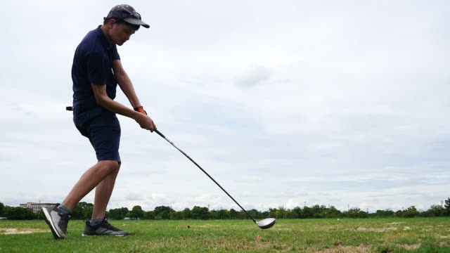 slow motion: hitting golf ball at golf course player exercise for good health - golf swing stock videos & royalty-free footage