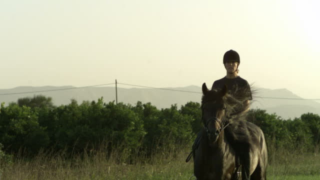 slow motion horse cantering with rider, mountain backdrop, spain (individual frames may also be used as a still image. each frame in its raw state is about 6mb or about 12mb as a 16 bit tiff) - horse bit stock videos and b-roll footage