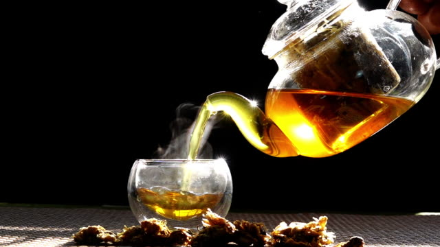 slow motion, hot chrysanthemum tea that is poured from a glass jar into a cup of white smoke from heat. - teapot stock videos & royalty-free footage