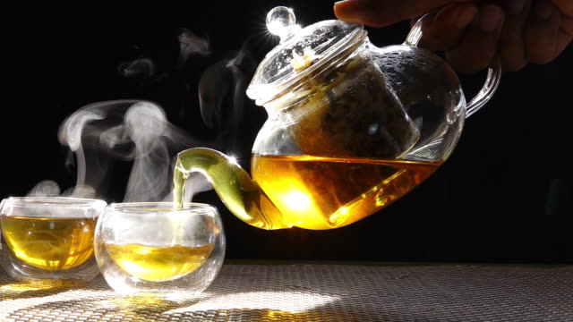 vídeos de stock e filmes b-roll de slow motion, hot chrysanthemum tea that is poured from a glass jar into a cup of white smoke from heat. - chávena de chá