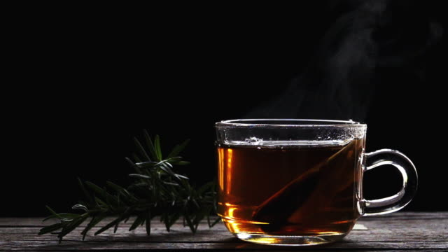 slow motion, hot rosemary tea cup on black background - tea cup stock videos & royalty-free footage
