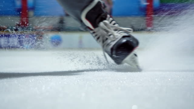 stockvideo's en b-roll-footage met 4k slow motion ijshockeyspeler close-up oefenen om te stoppen met schaatsen in de ijsbaan - surface level
