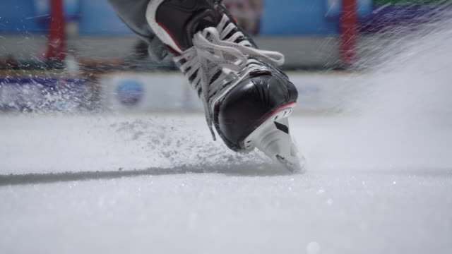 4k slow motion ice hockey player close up practicing to stop skating in the ice rink - sliding stock videos & royalty-free footage