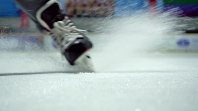 4k slow motion ice hockey player close up practicing to stop skating in the ice rink - ice skating stock videos & royalty-free footage