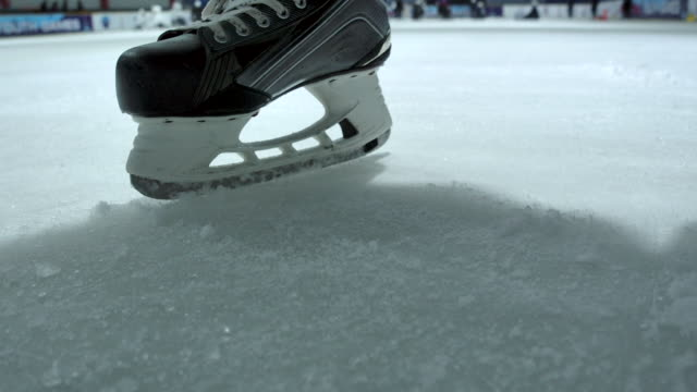4k slow motion ice hockey player close up practicing to stop skating in the ice rink - surface level stock videos & royalty-free footage