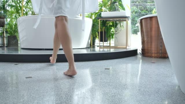 4k slow motion al mattino, la donna si è avvicinata alla vasca da bagno e si è tolsa la veste bianca per fare la doccia. - bagno video stock e b–roll