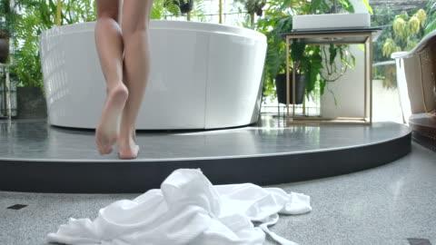 vídeos y material grabado en eventos de stock de 4k cámara lenta por la mañana, la mujer caminó hacia la bañera y se quitó la túnica blanca para tomar una ducha. - balneario spa