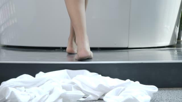 vídeos de stock, filmes e b-roll de 4k câmera lenta na parte da manhã, a mulher caminhou até a banheira e tirou o manto branco para tomar um banho. - despindo se