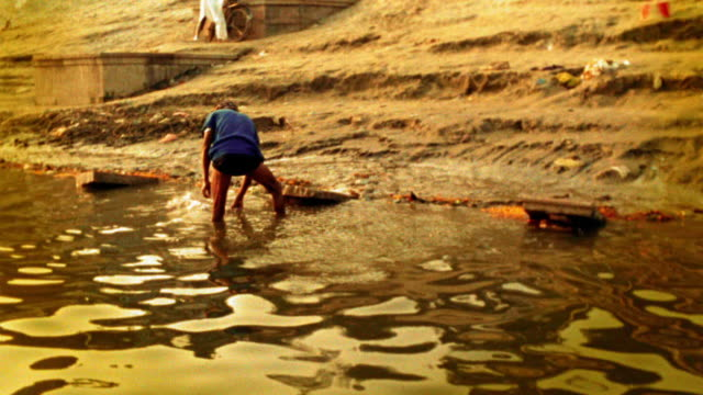 slow motion indian man washing cloth in ganges river / beating it on rock / varanasi, india - flussufer stock-videos und b-roll-filmmaterial