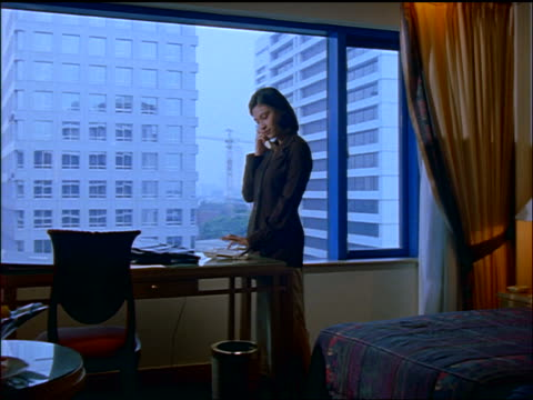 slow motion indonesian businesswoman talking on telephone by window in hotel room / jakarta - 東洋民族点の映像素材/bロール