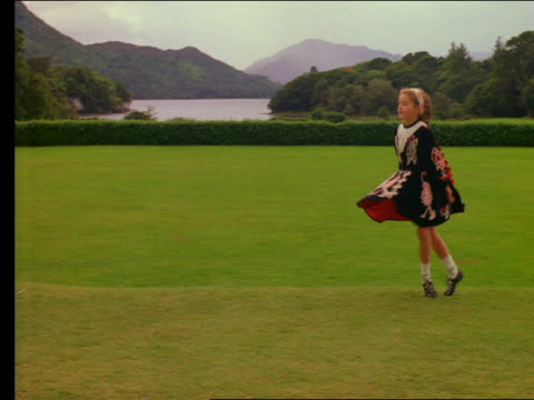 slow motion irish girl dancing a jig in grass - アイルランド共和国点の映像素材/bロール