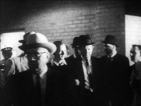 B/W 1963 slow motion Jack Ruby shooting killing Lee Harvey Oswald indoors / newsreel