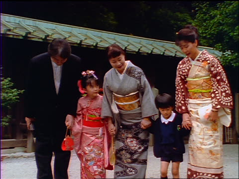 slow motion Japanese family bowing to camera / men in Western dress + women in kimonos