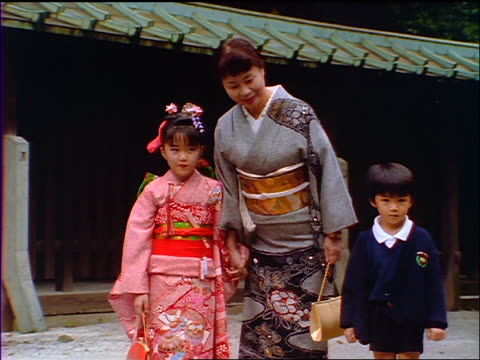 slow motion japanese mother with daughter in kimono + schoolboy bowing to camera / japan - respect点の映像素材/bロール
