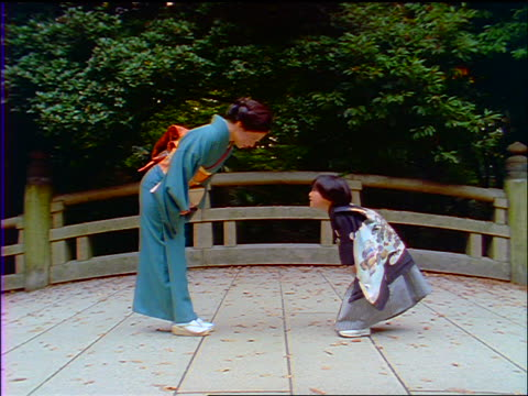 slow motion japanese woman in kimono + boy in traditional dress bowing to each other outdoors / japan - respect stock videos and b-roll footage