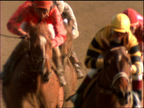 slow motion  jockeys on horses racing toward camera
