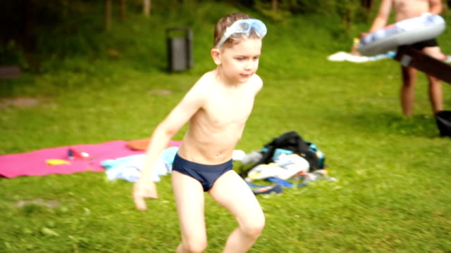 slow motion: kid enters the lake by running - gara sportiva individuale video stock e b–roll