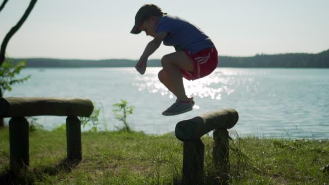 vídeos de stock e filmes b-roll de slow motion: kid jumping obstacle - água parada