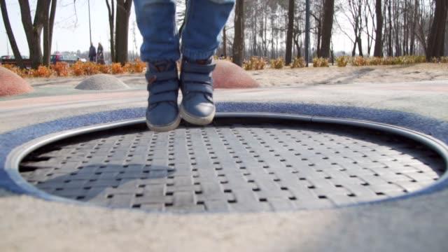 stockvideo's en b-roll-footage met slow motion: kid benen op het trampoline springen - trampoline