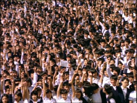 slow motion large crowd of Asian schoolchildren waving hands / Japan