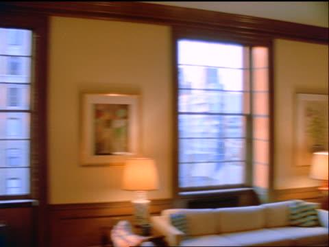 vídeos de stock e filmes b-roll de slow motion pan large living room filled with bookshelves in apartment - interiores em exposição