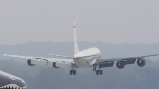 slow motion large white us air force cargo plane takes off from runway of military base. - cargo aeroplane stock videos & royalty-free footage